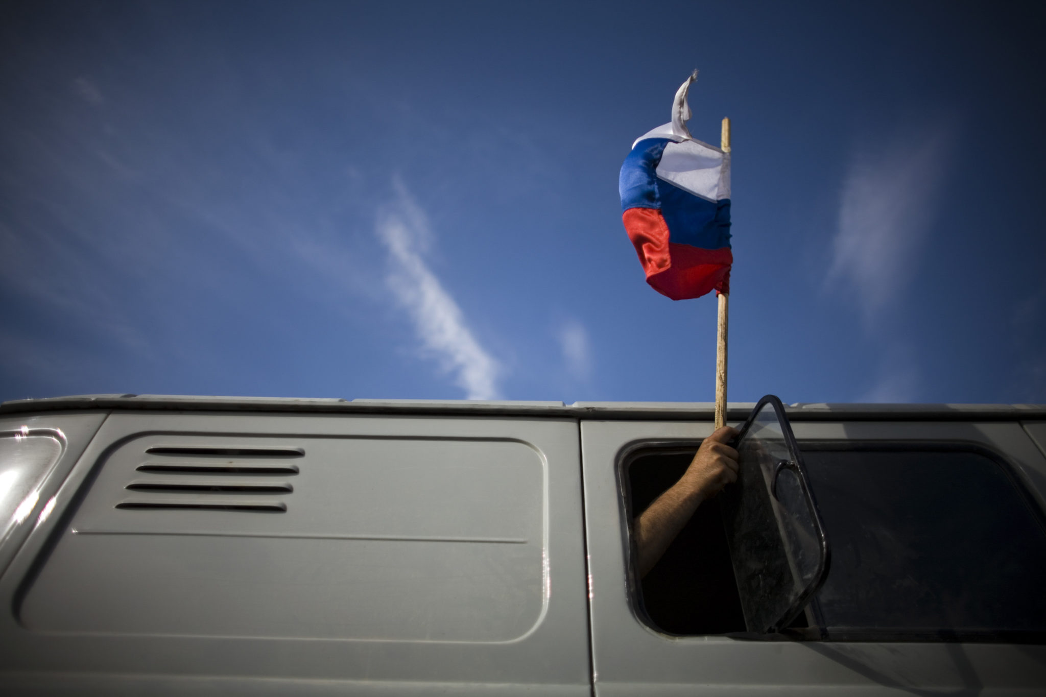 Man waving a flag of Russian federation out of a passing car at the entrance to the town of Gori.